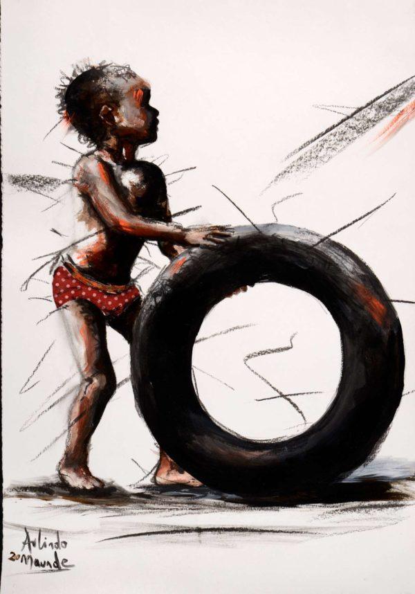 Little African boy playing with an old tyre