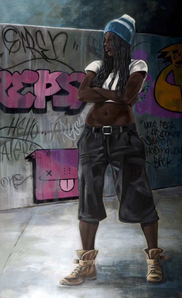 African woman standing in front of a wall covered in graffiti
