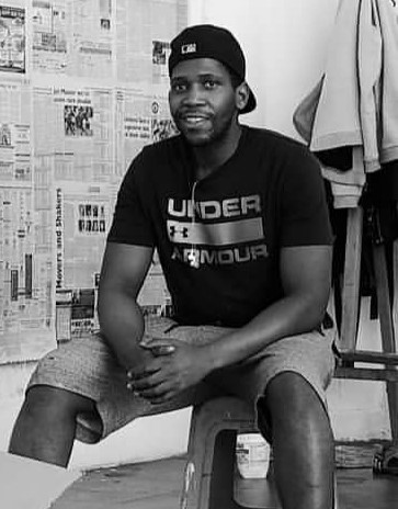 Andrew Ntshabele sitting on a chair in his studio