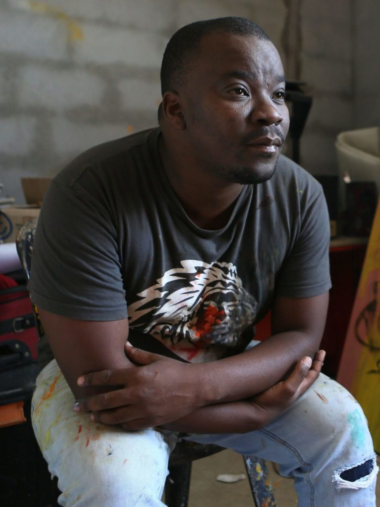 Khaya Sineyile sitting on a chair during an interview