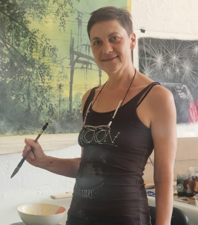 Nicola Holgate standing with a paint brush in her hand
