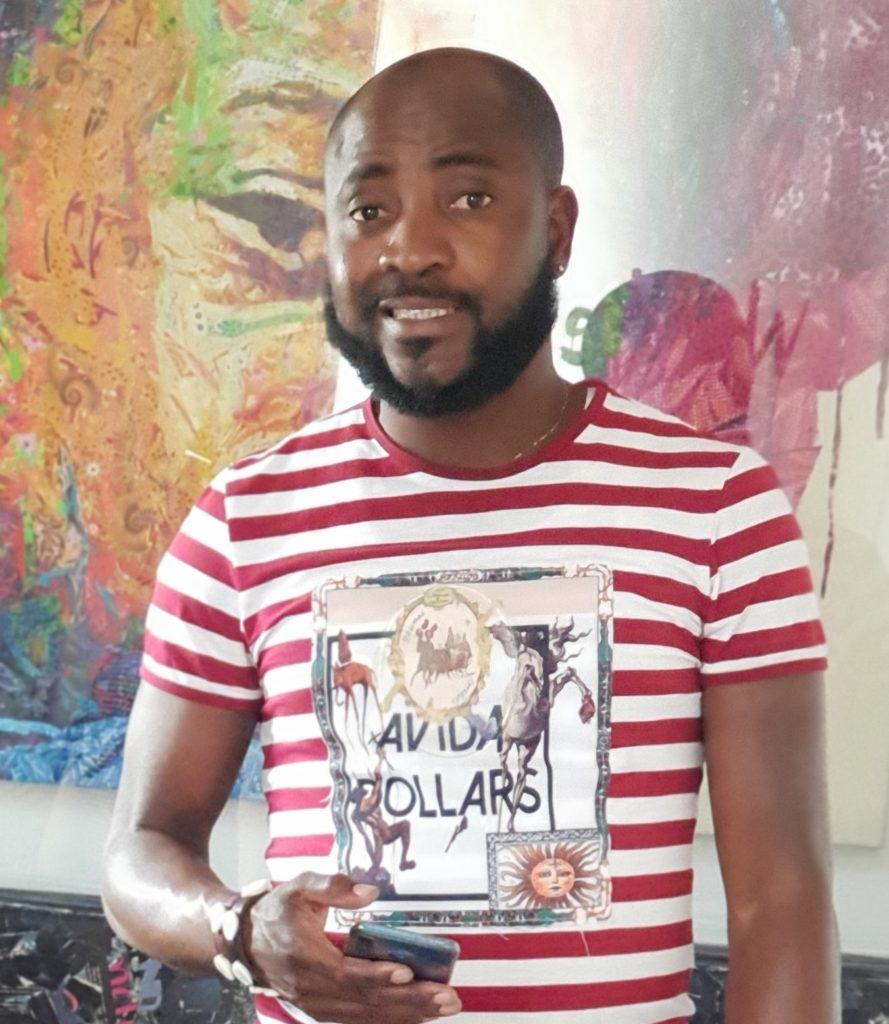 Sanusi Olantunji smiling in front of his painting