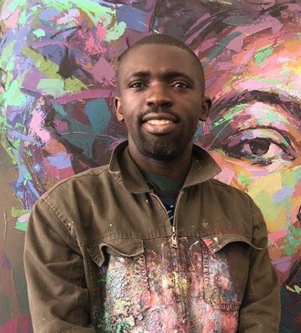 Solomon Omobogje standing in front of his painting