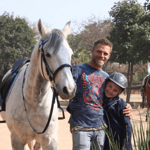 Nikodemis van Rensburg standing with a horse and smiling